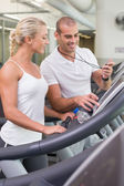 Male trainer timing his client on treadmill at gym — Stock Photo