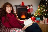 Ruiva alegre lendo na poltrona no Natal — Fotografia Stock