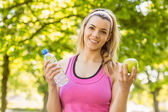 Fit blonde holding water and apple — Stock Photo