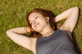 Pretty redhead lying with her eyes closed — Stock Photo