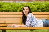 Casual brunette lying on bench typing on laptop — Stock Photo