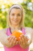 Fit blonde holding an orange — Stock Photo