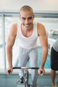Man working out on exercise bike at gym — Stock Photo