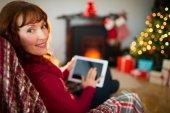 Beauty redhead using tablet at christmas — Stock Photo