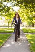 Pretty redhead cycling a bike — Stock Photo