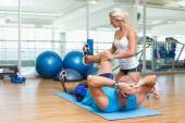 Trainer assisting man with exercises at fitness studio — Stock Photo