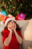 Red hair in santa hat relaxing on the couch at christmas — Stock Photo