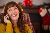 Happy redhead on the phone at christmas — Stock Photo