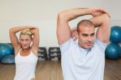 Couple stretching hands behind back in yoga class — Stockfoto