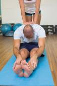 Trainer assisting man with stretching exercises at fitness studi — Stock Photo