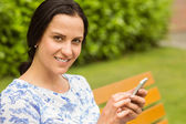 Smiling brunette using her smartphone — Stock Photo
