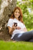 Pretty redhead text messaging on her phone  — Stock Photo