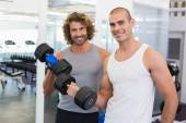 Sporty men exercising with dumbbells in gym — Foto Stock