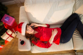 Redhead lying on the couch phoning at christmas  — Zdjęcie stockowe