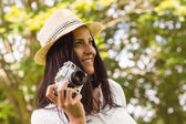 Smiling brunette in straw hat holding retro camera  — Stock Photo