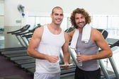 Smiling male trainer and fit man at gym — Foto de Stock