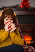 Beauty redhead drinking hot drink at christmas — Stock Photo