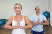 Couple with joined hands and eyes closed at fitness studio — Stock Photo