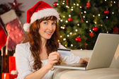 Smiling redhead shopping online with laptop — Zdjęcie stockowe