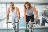 Fit men working on exercise bikes at gym — Stock Photo