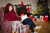 Smiling redhead reading on the armchair at christmas — Stock Photo