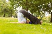 Brown hair doing yoga on grass — Photo