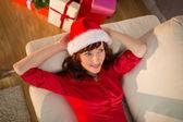 Rothaarige in Nikolausmütze entspannen auf der Couch zu Weihnachten — Stockfoto