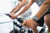 Mid section of men working on exercise bikes at gym — Stock Photo