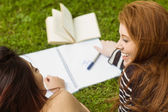 Female students with books in park — Stockfoto