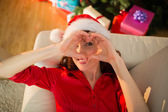 Smiling redhead doing heart sign at christmas — Stock Photo