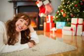 Smiling redhead woman lying on floor at christmas — Stock fotografie