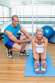 Trainer assisting woman with exercises at fitness studio — Stock Photo