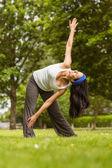 Relaxed brunette doing yoga on grass — ストック写真