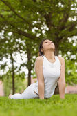 Woman doing stretching exercises at park — Stockfoto