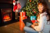 Redhead woman sitting on floor using laptop at christmas — Foto de Stock