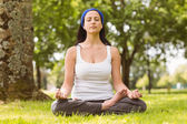 Fit brunette sitting in lotus pose on grass — Stock Photo