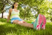 Happy brunette in sportswear relaxing on the grass — Stock Photo