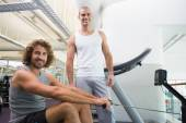Male trainer assisting man on fitness machine at gym — Stock Photo