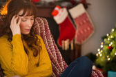 Unhappy redhead getting a headache at christmas — Stock Photo