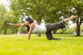 Brunette in balance pose on grass — Stock Photo