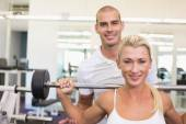 Trainer helping woman with lifting barbell in gym — Foto de Stock