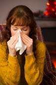 Woman sitting on sofa and blowing her nose at christmas — Foto de Stock