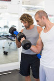 Sporty men exercising with dumbbells in gym — Stock Photo