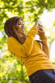 Woman text messaging in park — Stock Photo