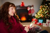 Calm redhead text messaging at christmas — Stock Photo