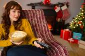 Pretty redhead watching television on couch at christmas — Stockfoto