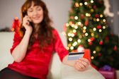 Smiling redhead phoning and holding credit card — Stockfoto