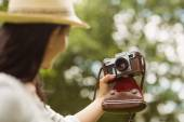 Brunette in straw hat taking a selfie with retro camera — Stock Photo