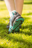 Woman in running shoes stepping on grass — Stock Photo