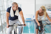 Fit couple working on exercise bikes at gym — Foto de Stock